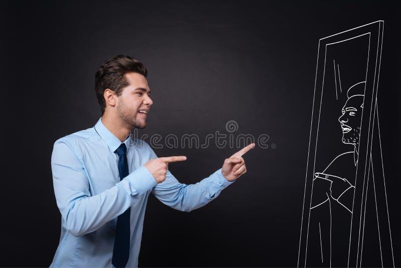 Homem novo considerável que olha em um espelho foto de stock royalty free