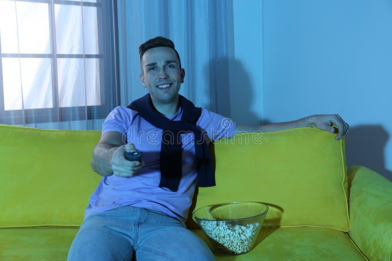 Homem novo considerável que olha a tevê no sofá fotos de stock