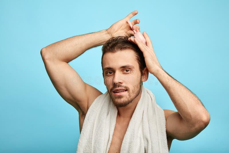 Homem novo considerável que penteia seus cabelo e agter de sorriso que tomam o chuveiro imagens de stock royalty free