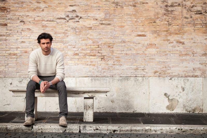Homem novo considerável que senta-se no banco de mármore com fundo dos tijolos fotografia de stock