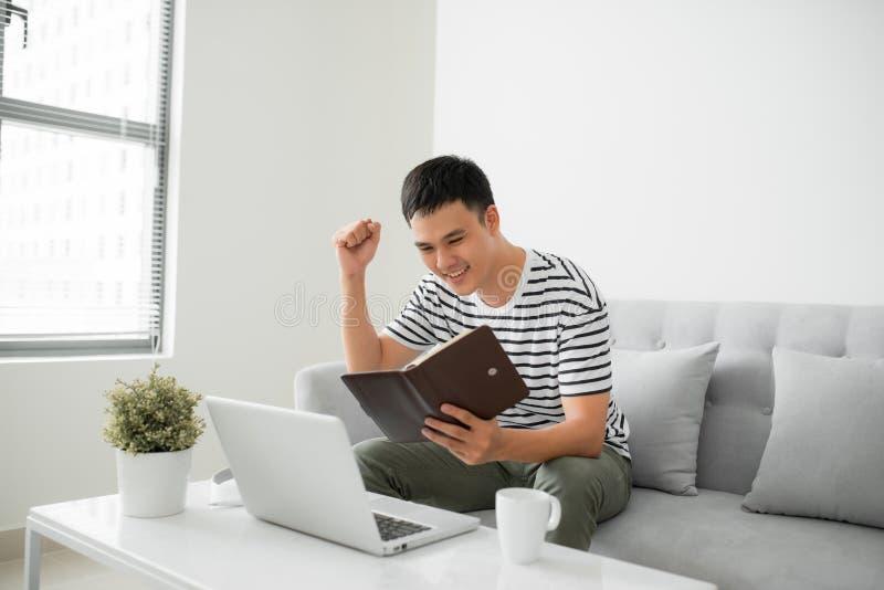 Homem novo considerável que senta-se no sofá da sala de visitas, escrevendo algumas notas ao olhar seu laptop foto de stock