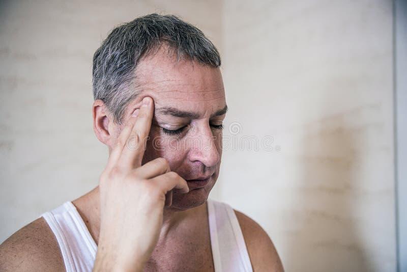 Homem novo considerável que toca em sua cabeça com a uma mão que sente a dor de cabeça forte, fim acima da foto imagem de stock