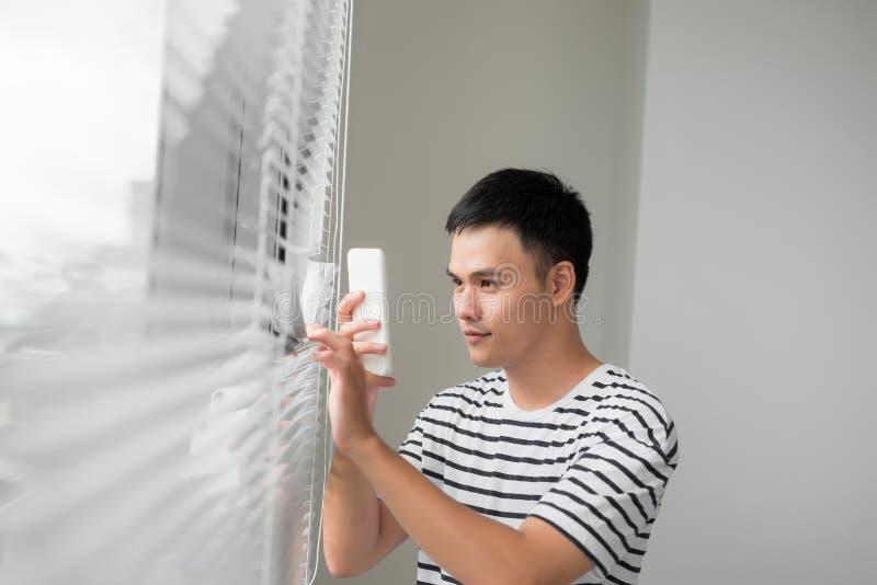 Homem novo considerável que toma a foto através da janela com móbil imagens de stock royalty free