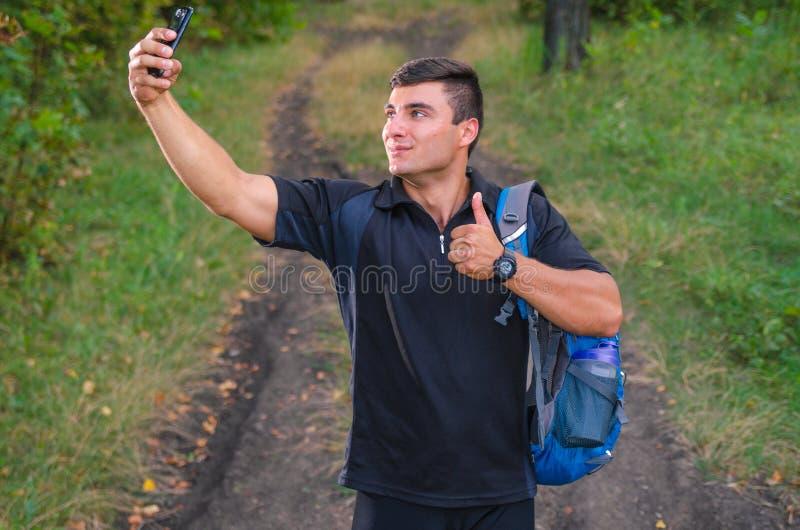 Homem novo considerável que toma um selfie com um telefone, sorrindo classificado com um alargamento, no estilo do instagram imagens de stock