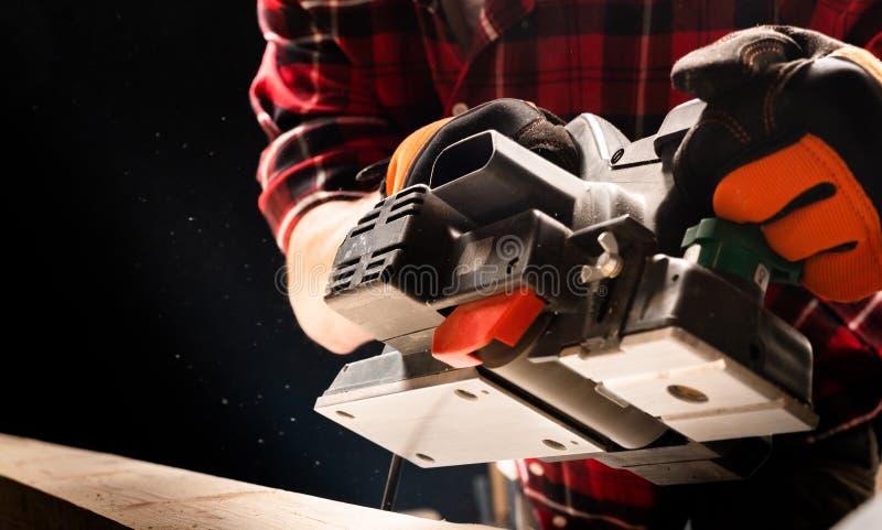 Homem novo considerável que usa a máquina de lixar de lixamento de madeira da correia das máquinas fotografia de stock royalty free