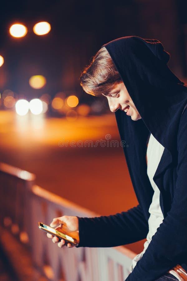 Homem novo considerável que usa o smartphone na cidade foto de stock