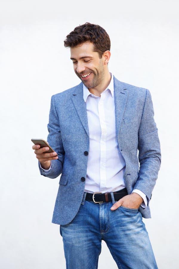 Homem novo considerável que usa o telefone celular no fundo branco foto de stock royalty free