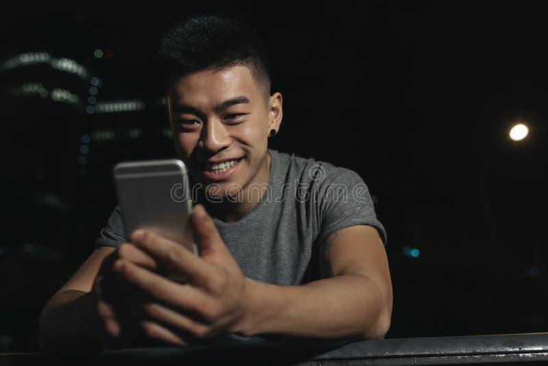 Homem novo considerável que usa seu móbil foto de stock