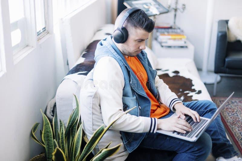 Homem novo consider?vel que usa o laptop com auriculares imagem de stock royalty free