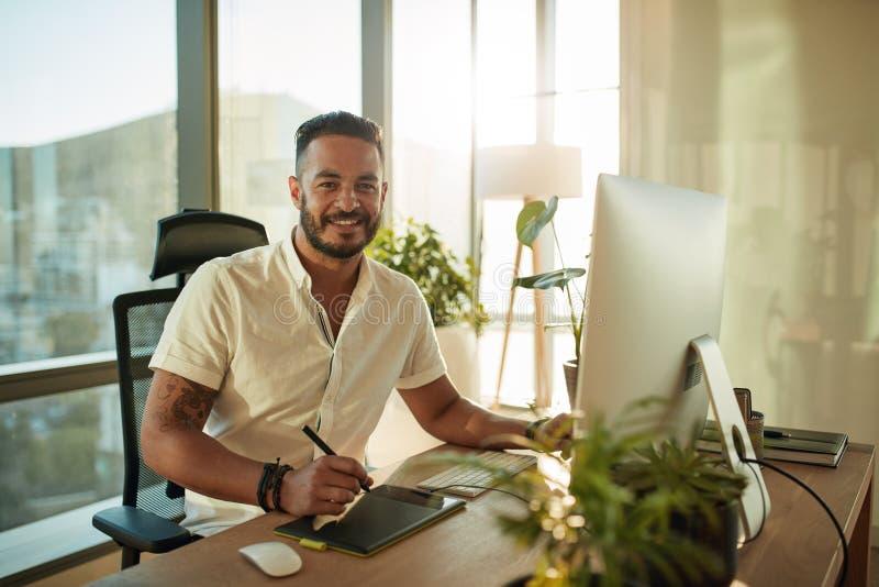 Homem novo criativo que trabalha no escritório com tabuleta gráfica fotografia de stock royalty free