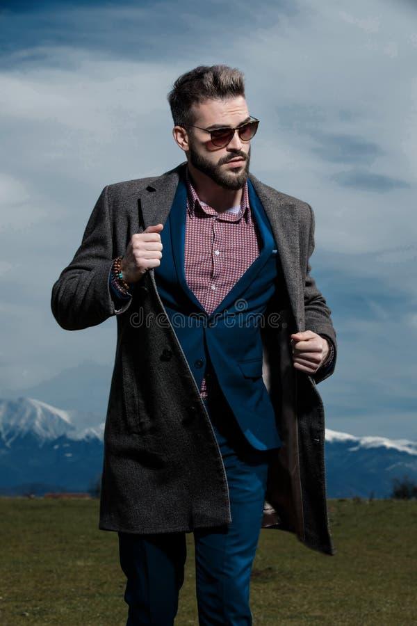 Homem novo curioso que anda e que olha ao lado fotografia de stock royalty free