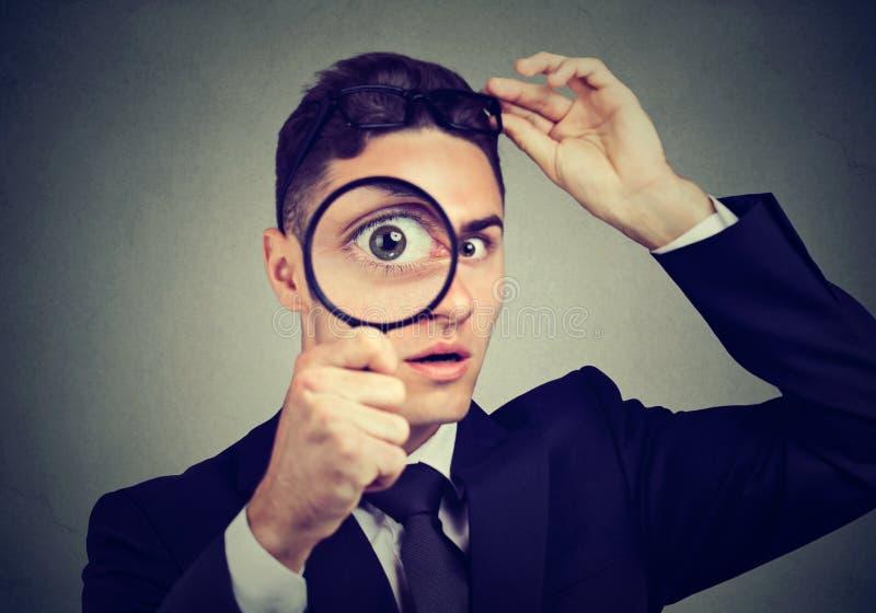 Homem novo curioso que descola os vidros que olham através de uma lupa imagens de stock
