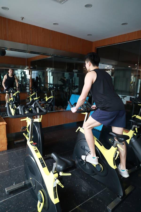 Homem novo da aptidão chinesa asiática no giro da bicicleta do gym fotografia de stock