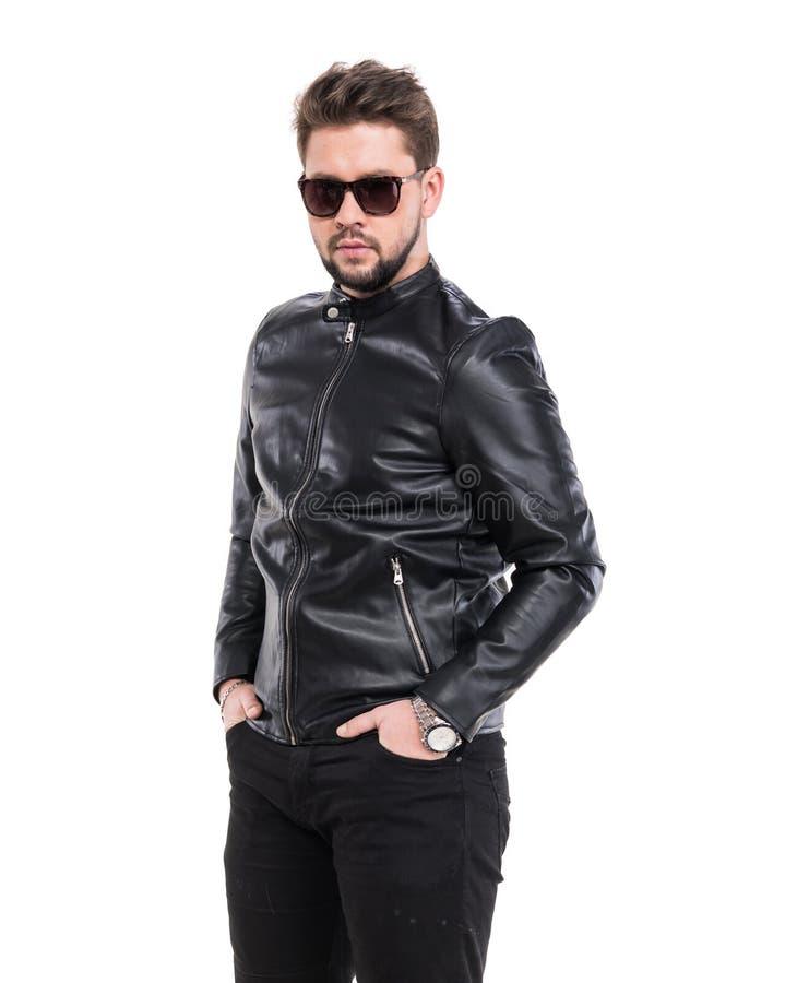 Homem novo da barba nos óculos de sol que vestem o casaco de cabedal preto fotos de stock