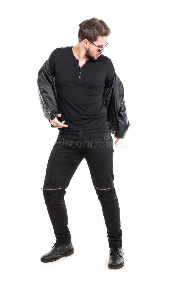 Homem novo da barba nos óculos de sol que vestem o casaco de cabedal preto imagem de stock royalty free
