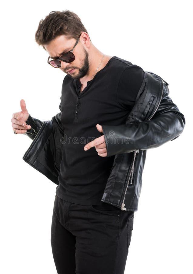 Homem novo da barba nos óculos de sol que vestem o casaco de cabedal preto fotografia de stock royalty free