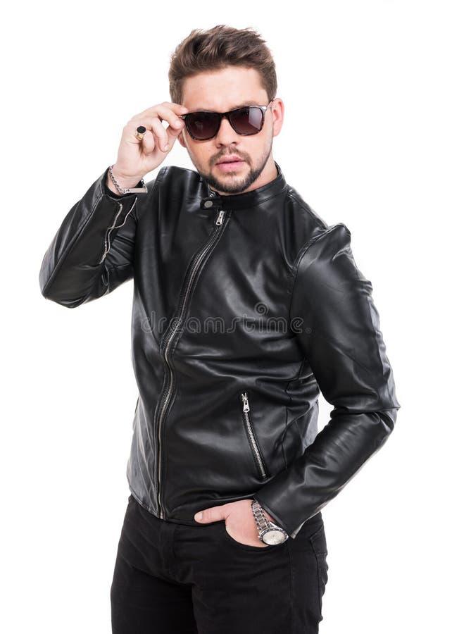 Homem novo da barba nos óculos de sol que vestem o casaco de cabedal preto fotos de stock royalty free