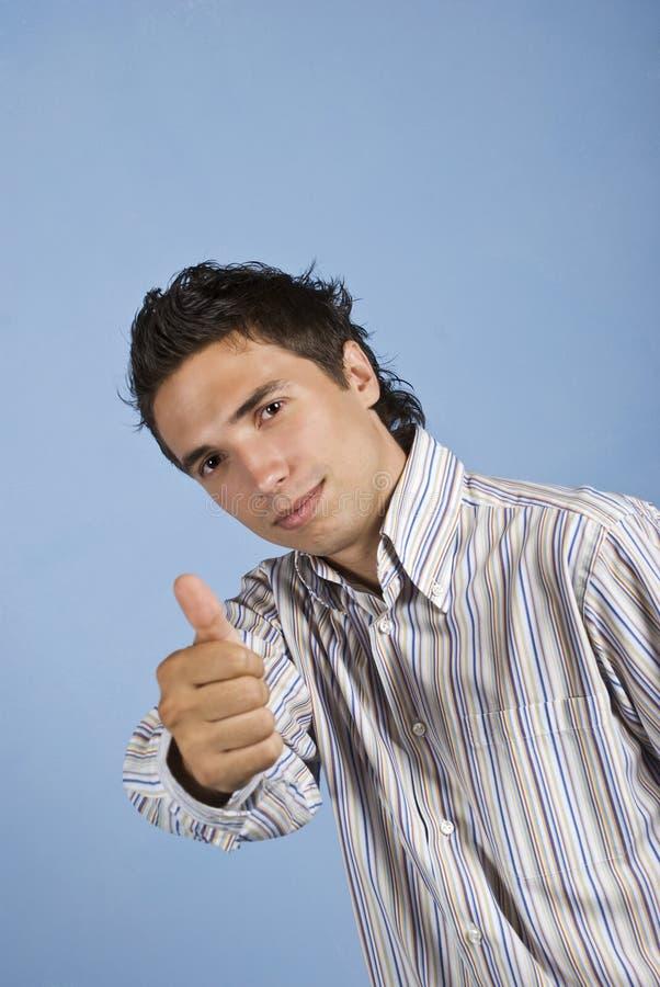 Homem novo da beleza que dá os polegares acima fotografia de stock royalty free