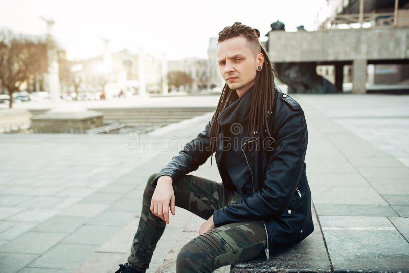 Homem novo da estrela do rock do balancim que anda no dia do outono da rua da cidade imagem de stock royalty free