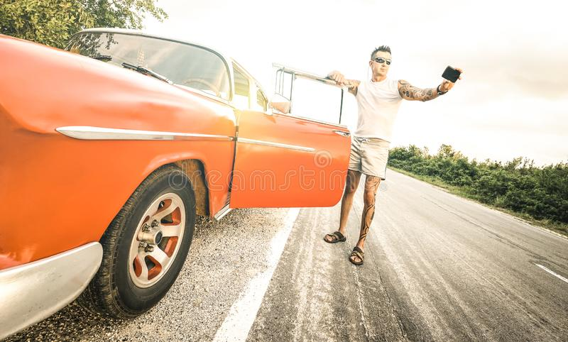 Homem novo da forma do moderno com a tatuagem que toma o selfie com o carro do vintage durante a viagem por estrada em Cuba - con imagem de stock royalty free