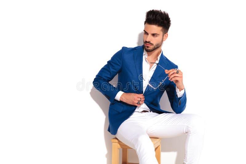 Homem novo da forma que senta-se na cadeira que fecha seu revestimento foto de stock