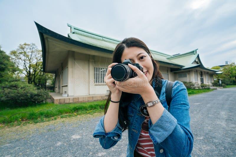 Homem novo da lente do turismo que toma a imagem pelo sorriso da câmera fotógrafo profissional atrativo alegre que usa o tiro do  imagem de stock royalty free