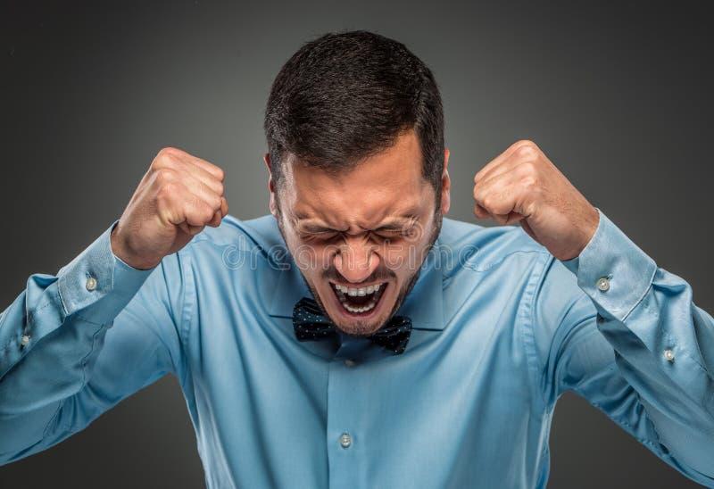 Homem novo da virada irritada do retrato na camisa azul, laço de borboleta fotos de stock