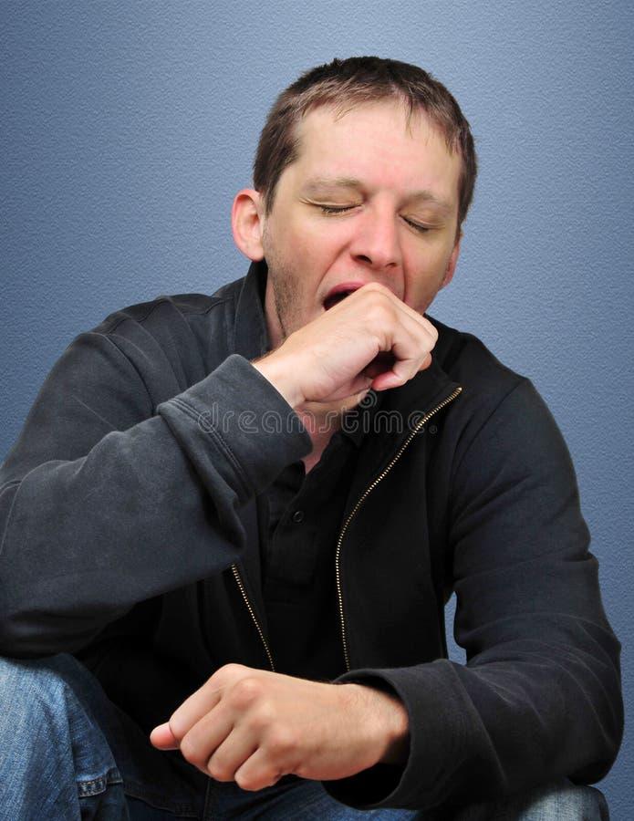 Homem novo de bocejo fotografia de stock