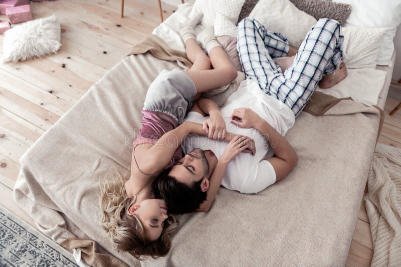 Homem novo de cabelo escuro considerável em uma camisa branca e no seu sono louro bonito da esposa foto de stock royalty free