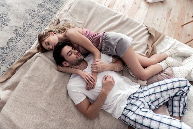 Homem novo de cabelo escuro considerável em uma camisa branca e em sua esposa loura bonito que colocam na cama foto de stock royalty free