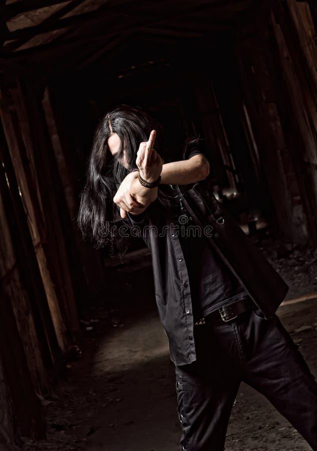 Homem novo de cabelos compridos que faz o gesto ofensivo (dedo médio) fotografia de stock