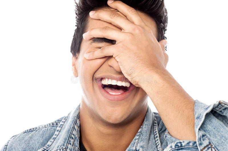 Homem novo de riso com mão em sua cara fotos de stock royalty free