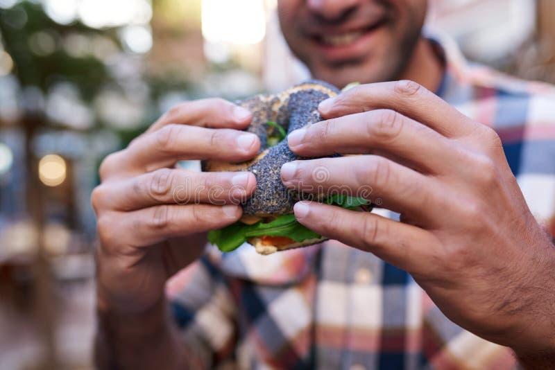 Homem novo de sorriso aproximadamente para comer fora um bagel delicioso fotos de stock