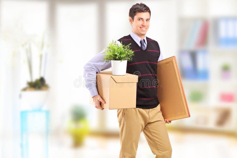 Um homem novo de sorriso com as caixas que movem-se em um apartamento fotos de stock royalty free