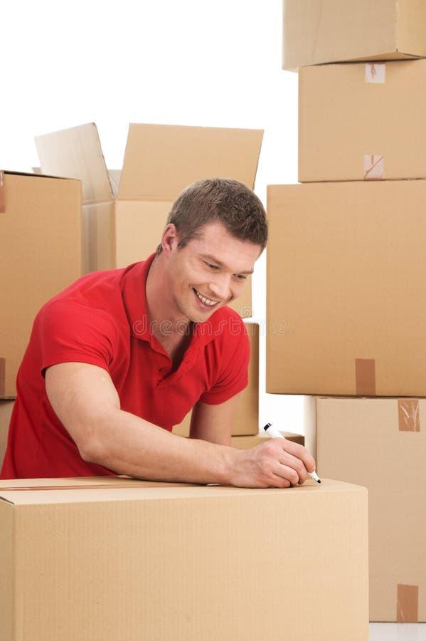 Homem novo de sorriso com caixa de cartão fotografia de stock royalty free