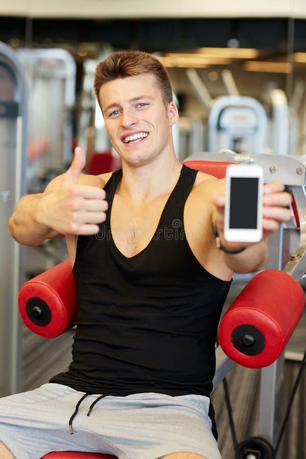 Homem novo de sorriso com o smartphone no gym imagens de stock royalty free