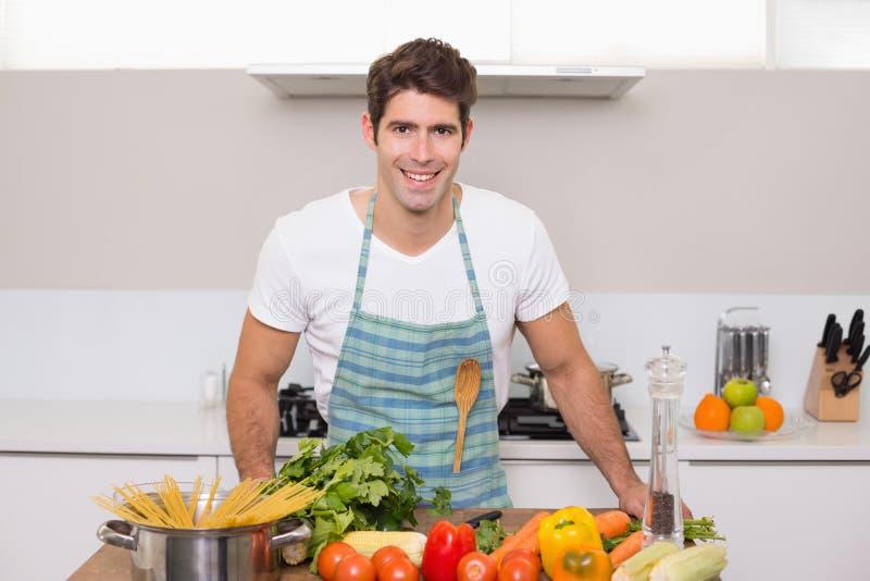Homem novo de sorriso com os vegetais que estão na cozinha imagens de stock