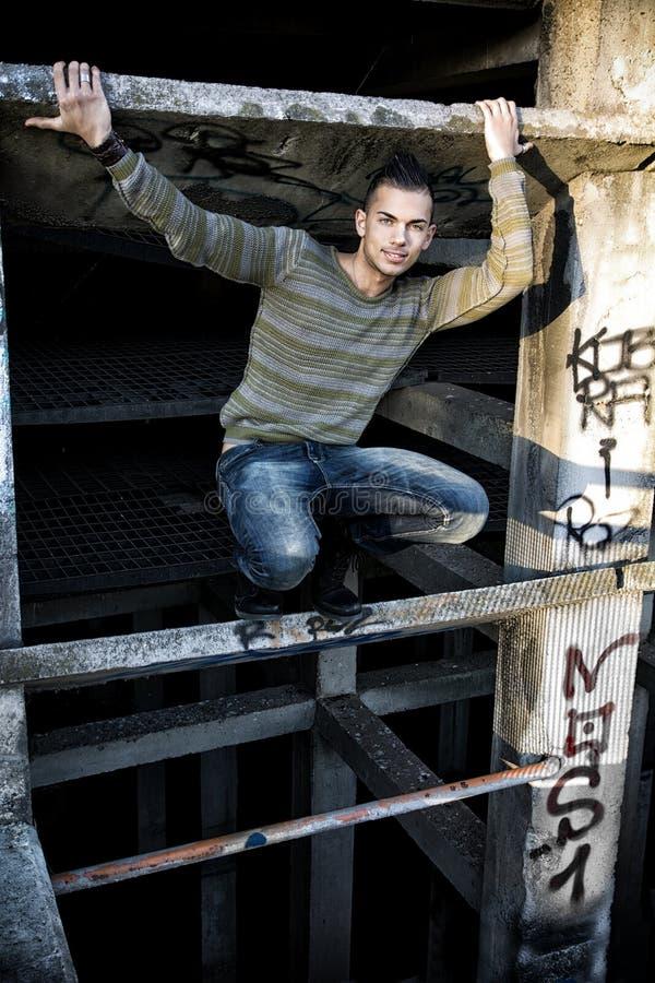 Homem novo de sorriso considerável no local industrial abandonado fotografia de stock royalty free
