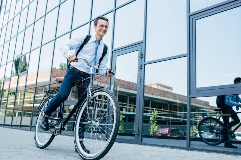 homem novo de sorriso considerável nos monóculos e na bicicleta da equitação do vestuário formal fotografia de stock