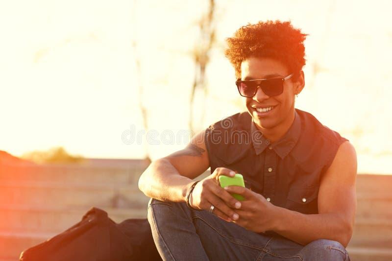 Homem novo de sorriso do moderno urbano que usa o telefone esperto imagens de stock royalty free