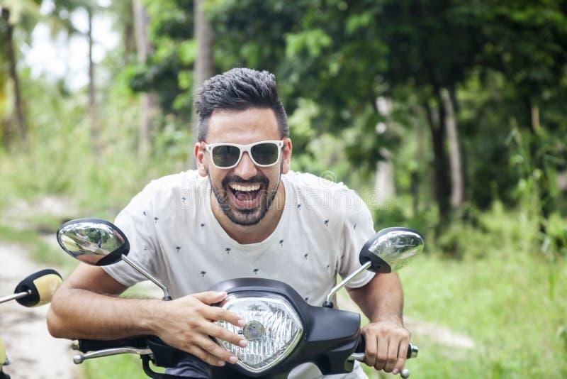 Homem novo de sorriso feliz atrativo em um velomotor na selva, feriados de raça misturada, felicidade, liberdade, estilo imagem de stock