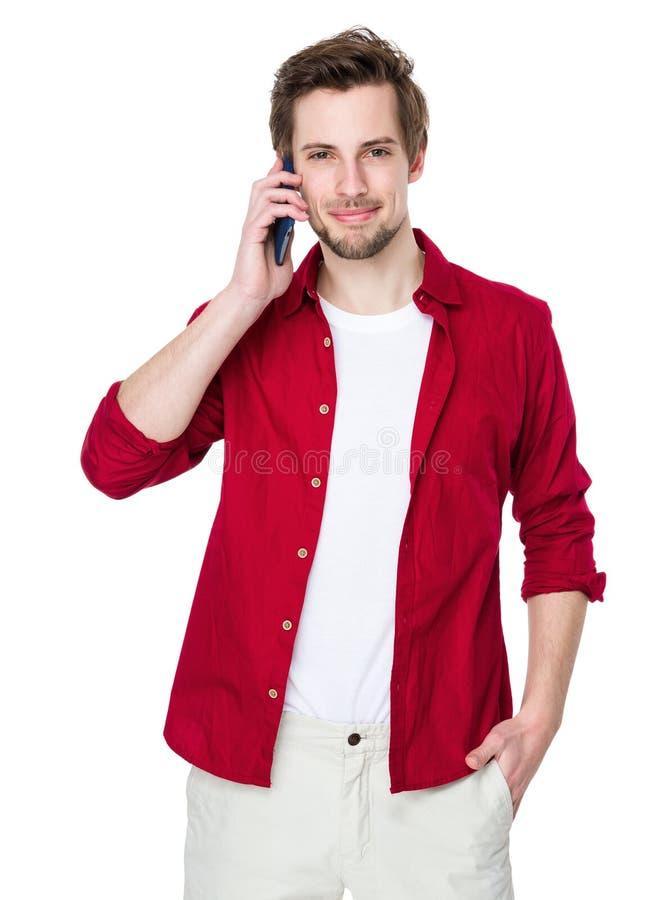 Homem novo de sorriso feliz que fala no móbil fotografia de stock