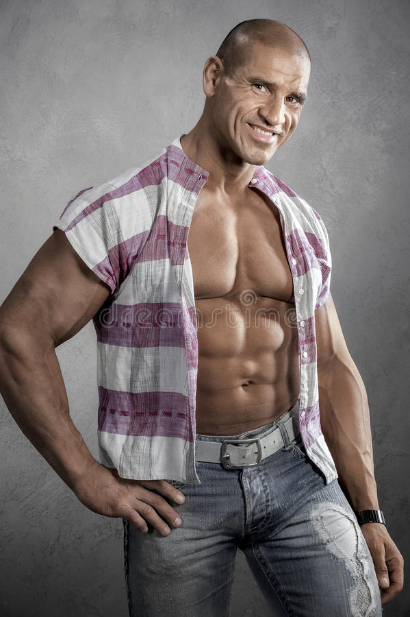 Homem novo de sorriso muscular contra o fundo cinzento foto de stock