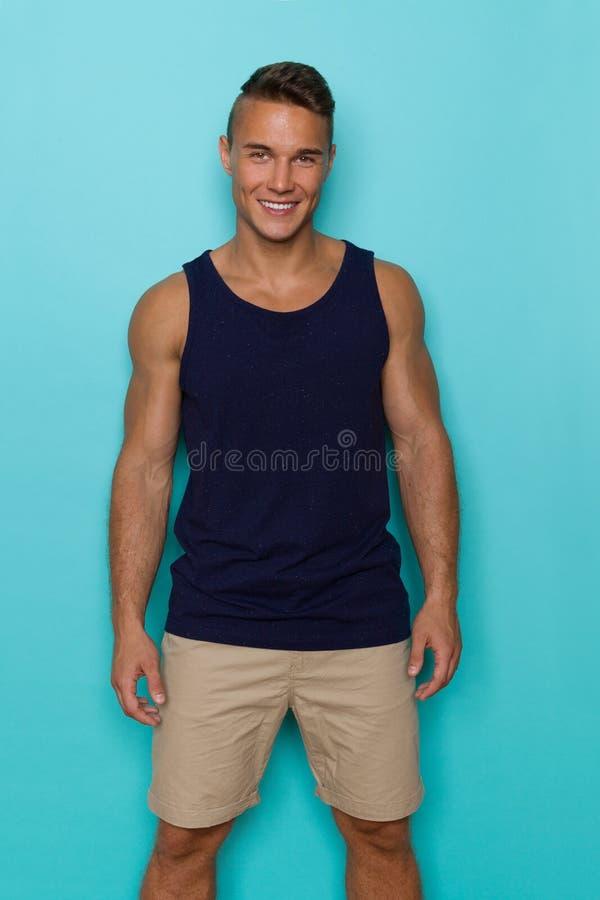 Homem novo de sorriso na camiseta de alças azul e no short bege fotografia de stock royalty free