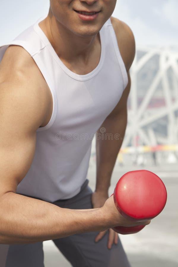 Homem novo de sorriso na camisola de alças branca que exercita com peso, close-up, seção mestra, fora no Pequim fotografia de stock