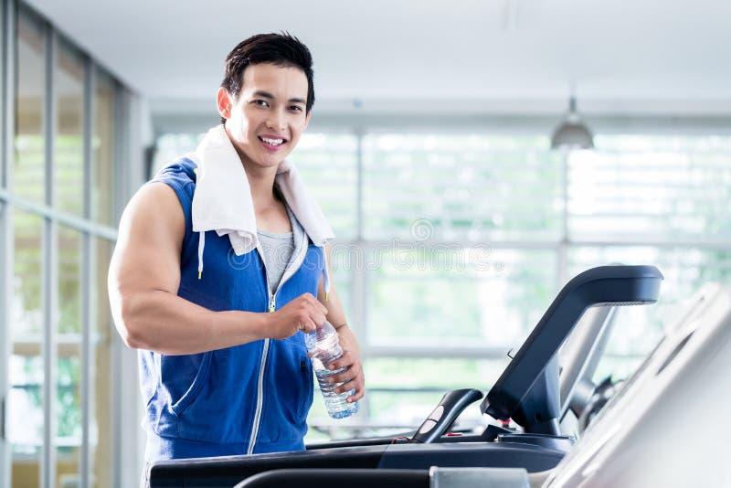 Homem novo de sorriso na escada rolante que guarda a garrafa de água fotografia de stock royalty free