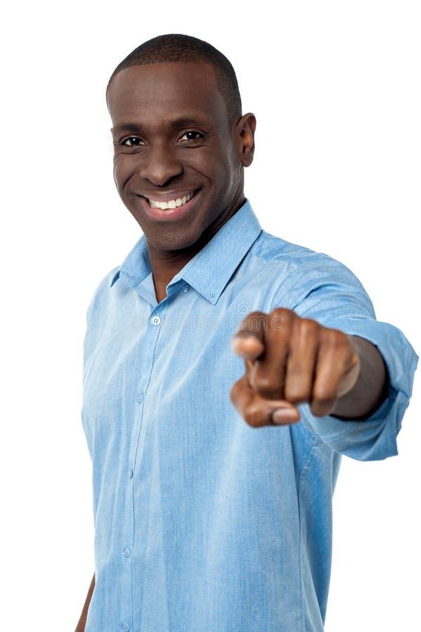 Homem novo de sorriso que aponta o para fora imagem de stock