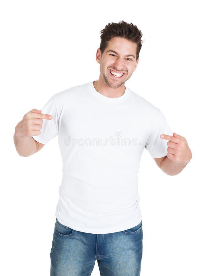 Homem novo de sorriso que aponta-se fotografia de stock