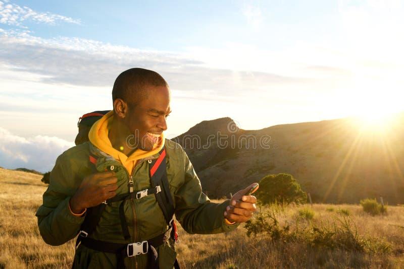 Homem novo de sorriso que caminha nas montanhas e em olhar o telefone celular fotografia de stock