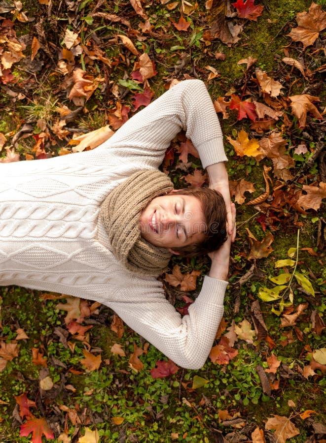 Homem novo de sorriso que encontra-se na terra no parque do outono foto de stock royalty free